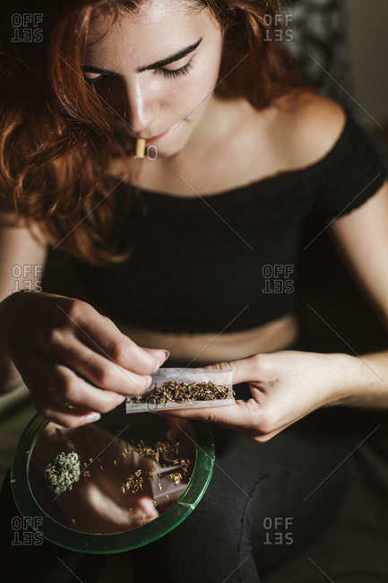 Young woman rolling a joint at home