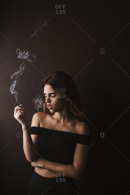 Young woman smoking marihuana at home