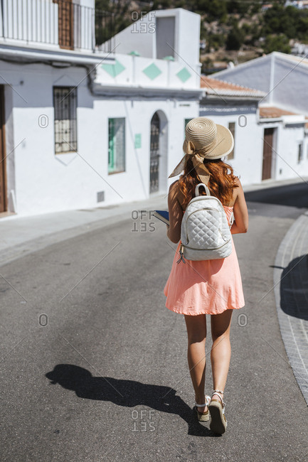 Back view of fashionable young tourist with backpack walking along the street- Frigiliana- Malaga- Spain