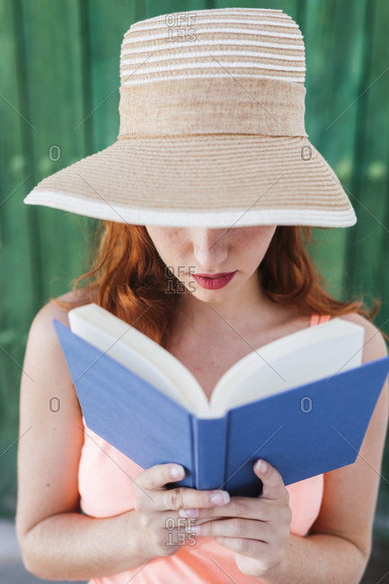 Redheaded young woman in front of green wooden door reading a book in summer
