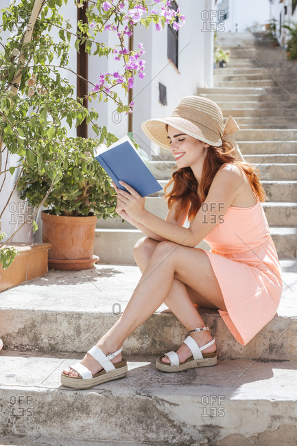Fashionable young woman sitting on stairs reading a book- Frigiliana- Malaga- Spain