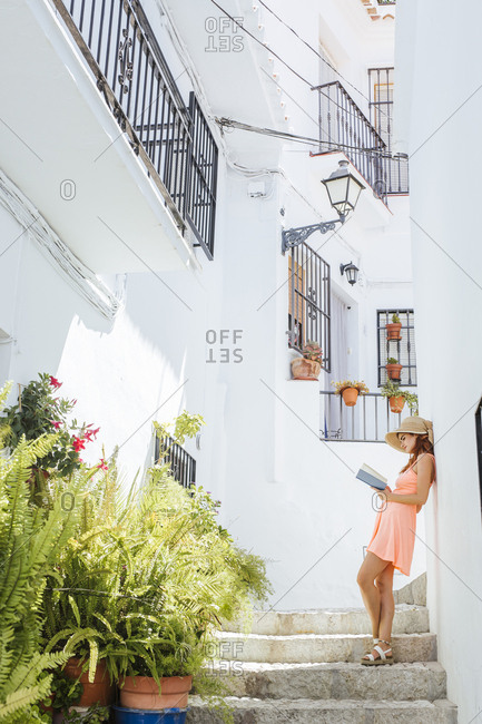 Fashionable young woman standing on stairs reading a book- Frigiliana- Malaga- Spain