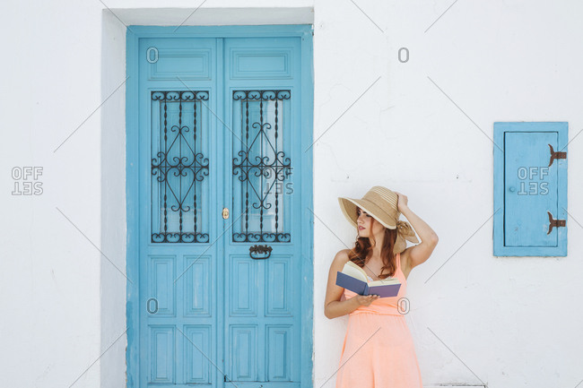 Redheaded young woman with book standing in front of a house looking at distance- Frigiliana- Malaga- Spain