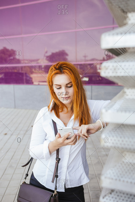 Business woman using smartphone in front of a modern commercial building