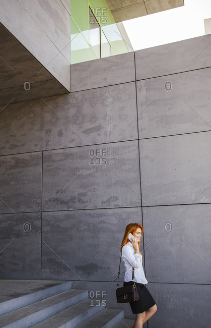Business woman going down stairs and using smartphone