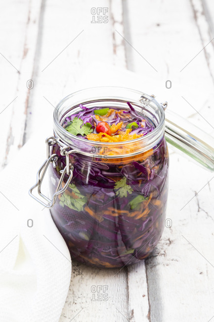 Jar of red cabbage- chili peppers- carrots and coriander on wooden table