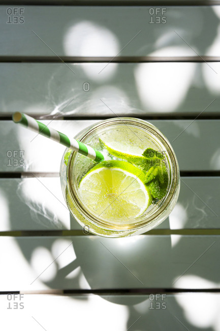 Glass of lime-mint lemonade on garden table