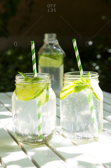 Two glasses of lime-mint lemonade on garden table