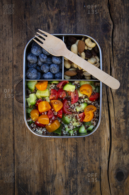 Directly above view of fresh meal in lunch box with fork on wooden table