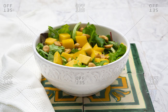 High angle view of fresh salad in bowl by napkin on tiled floor