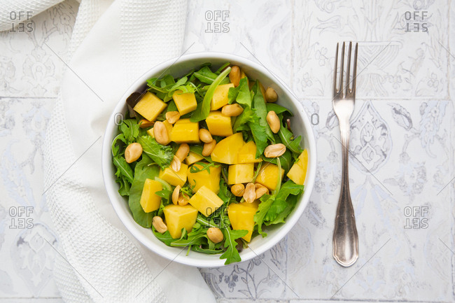 Close-up of fresh salad in bowl by napkin and fork on tiled floor