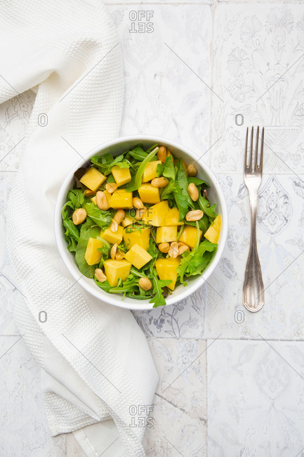 Directly above view of fresh salad in bowl amidst napkin and fork on tiled floor