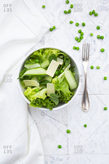 Directly above view of fresh salad in bowls by napkin and forks