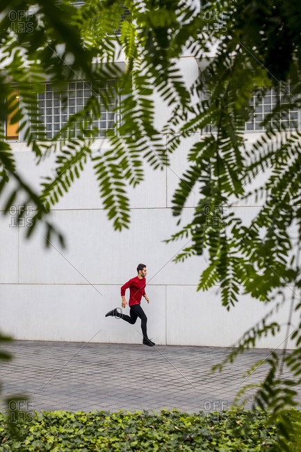 Young athlete doing intensive running training in the city