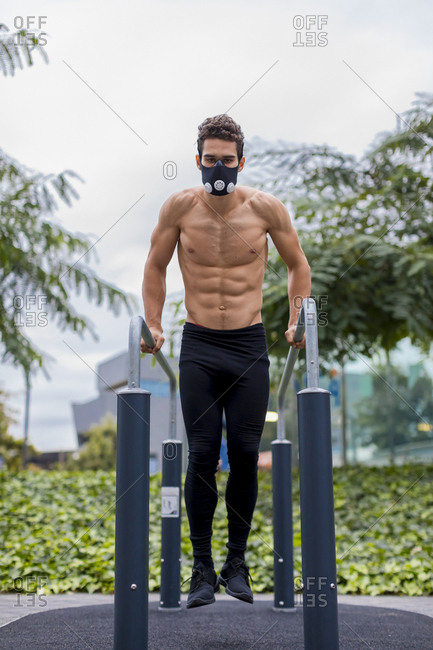 Athlete training on bars in the city- wearing breathing mask