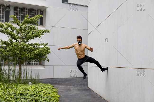 Athlete doing intense training with breathing mask- jumping against house wall