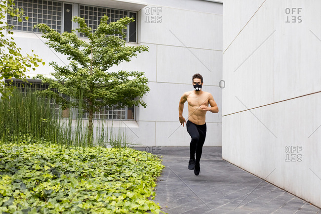 Young athlete doing intensive running training in the city- wearing breathing mask
