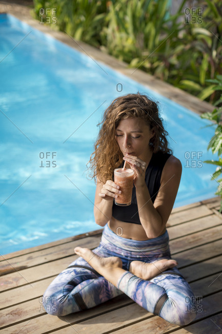 Woman practicing yoga at poolside- drinking juice- Costa Rica