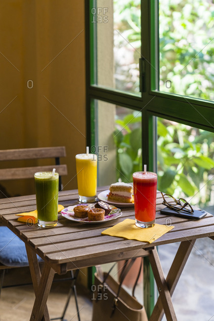 Variation of smoothies and cake on wooden table
