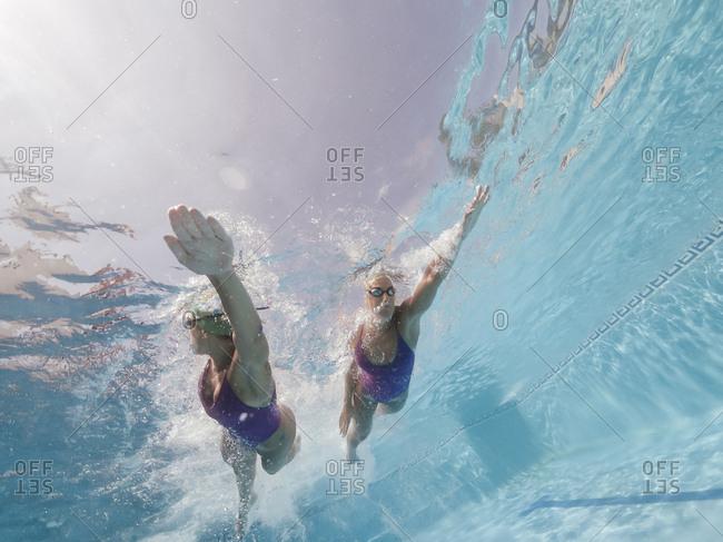Two women swimming in a pool
