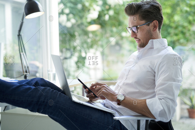 Businessman using laptop and smartphone in office
