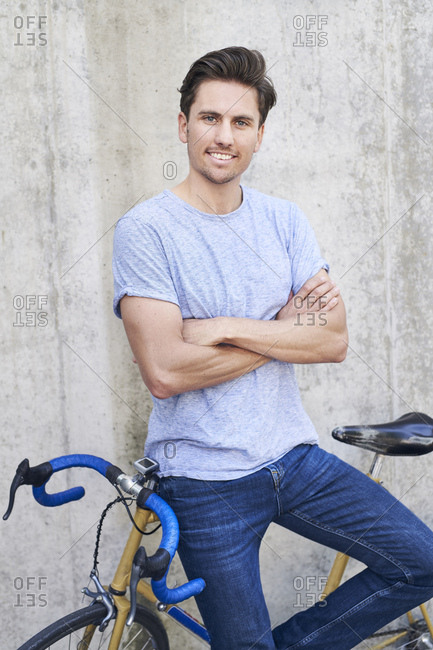 Portrait of smiling man with racing cycle standing in front of concrete wall