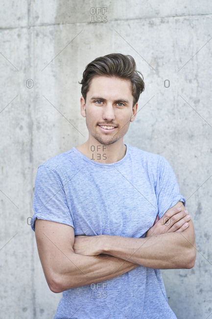 Portrait of man with arms crossed wearing grey t-shirt in front of concrete wall