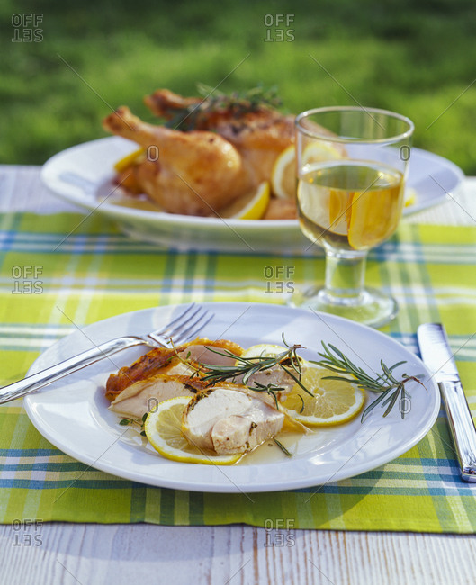 Roasted chicken in lemon sauce and glass of white wine on garden table
