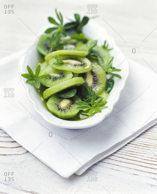 Dessert of fresh kiwi fruit and sweet-scented bedstraw leaves