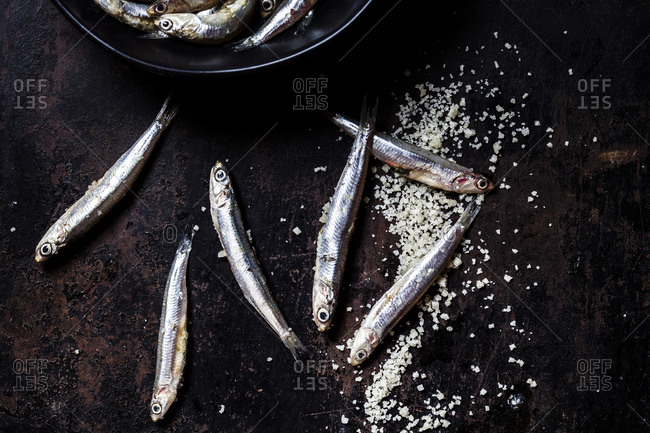 Close-up of fresh anchovies and sea salt on black slate rock
