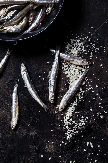 Directly above view of fresh anchovies and sea salt on slate rock