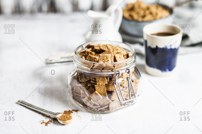 Close-up of fresh homemade baked cinnamon cereals in open jar by cup on table