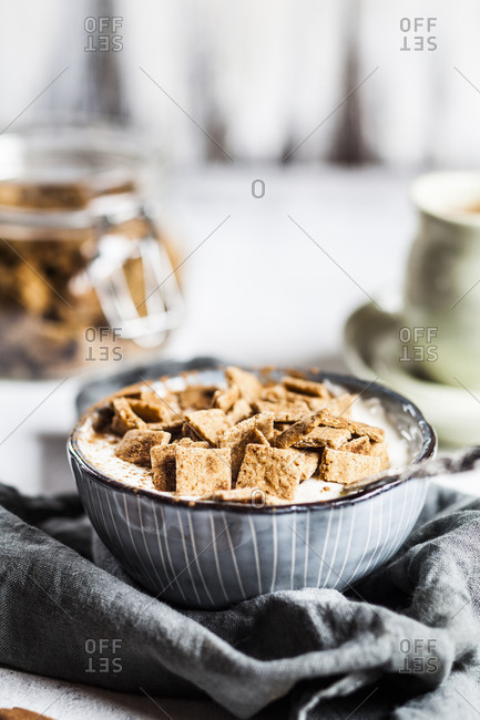 Close-up of fresh homemade baked cinnamon cereals with yogurt in bowl on napkin