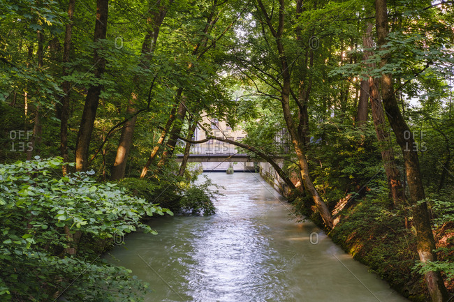Germany- Upper Bavaria- Munich- Trees surrounding canal withĘMuffathalle in background