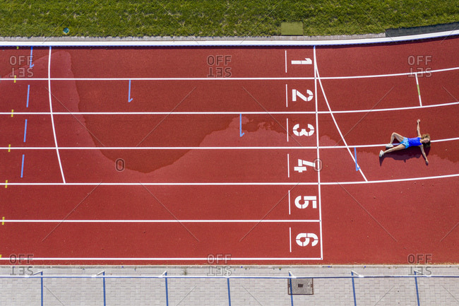 Aerial view of a young female athlete lying on a tartan track after crossing the finishing line