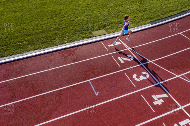 Aerial view of a running young female athlete on a tartan track crossing finishing line