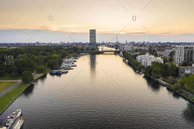 June 13, 2019: Spree river flowing amidst residential building seen from Treptower Park against sky during sunset