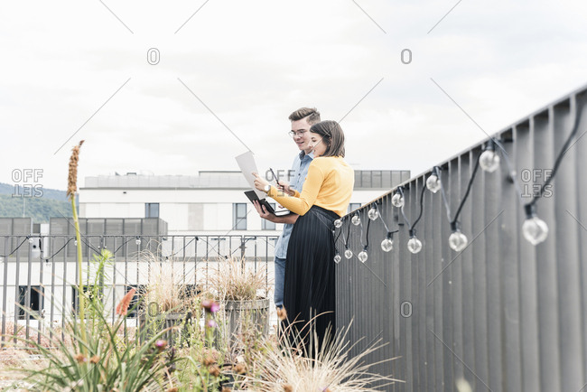 Casual businessman and woman with laptop and documents meeting on roof terrace