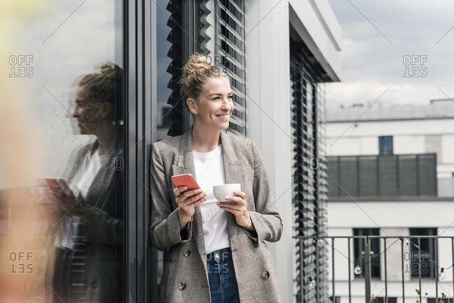 Smiling businesswoman with cell phone and coffee cup standing on roof terrace