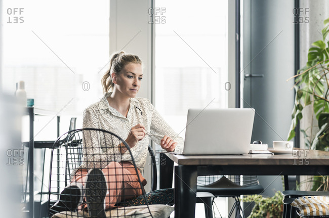 Businesswoman sitting at table in office using laptop