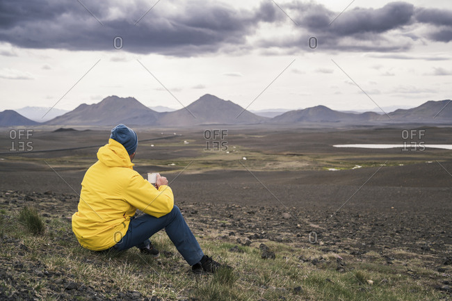 Man drinking coffee- looking at landscape in Iceland