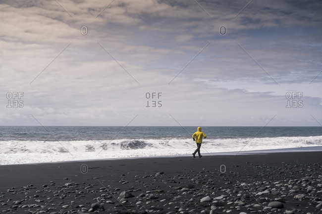 Mature man running on a lava beach in Iceland
