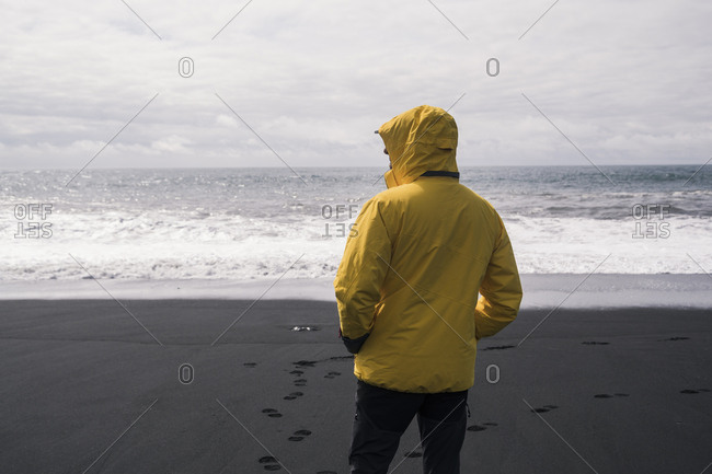 Mature man on a lava beach in Iceland- looking at the sea