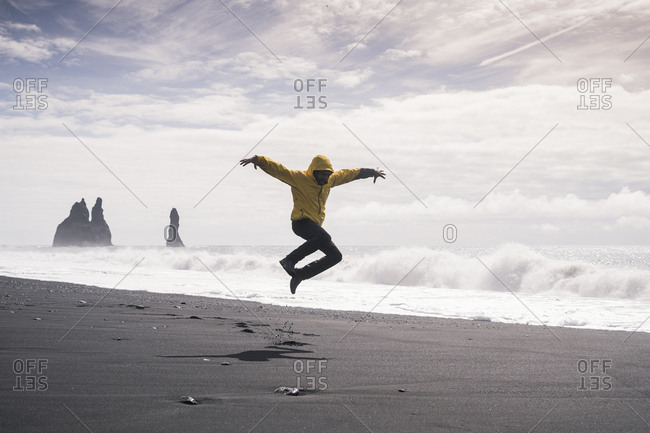 Mature man jumping for joy on a lava beach in Iceland