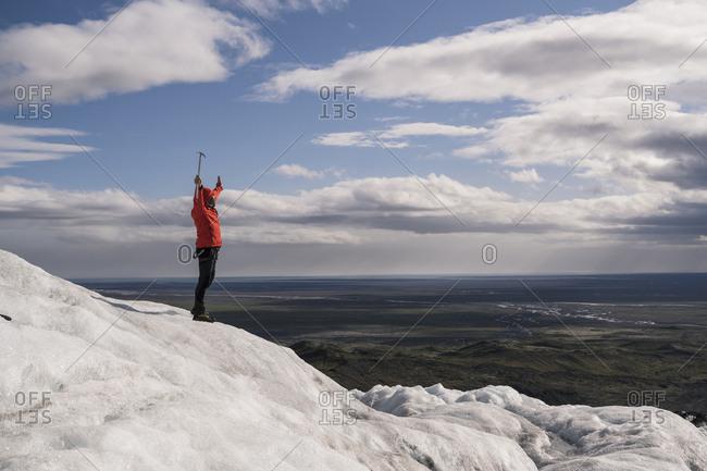 Mature man standing in Skaftafell National Park on Vatnajokull glacier- Iceland- holding ice ax