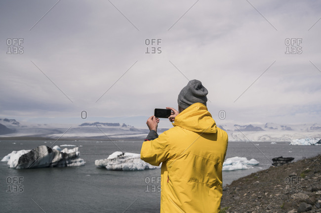 Mature man taking pictures of Vatnajokull glacier with binoculars- Iceland