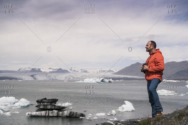 Mature man watching Vatnajokull glacier holding binoculars- Iceland