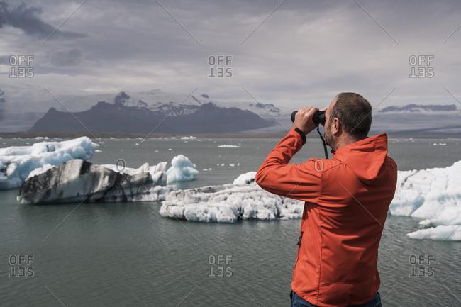 Mature man watching Vatnajokull glacier with binoculars- Iceland