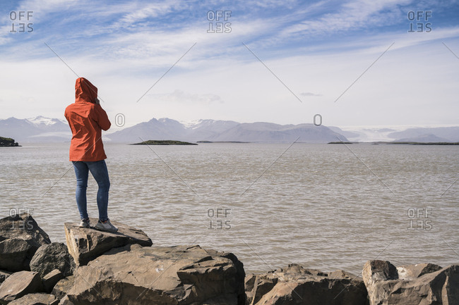 Young woman standig boulders- looking at the sea- South East Iceland