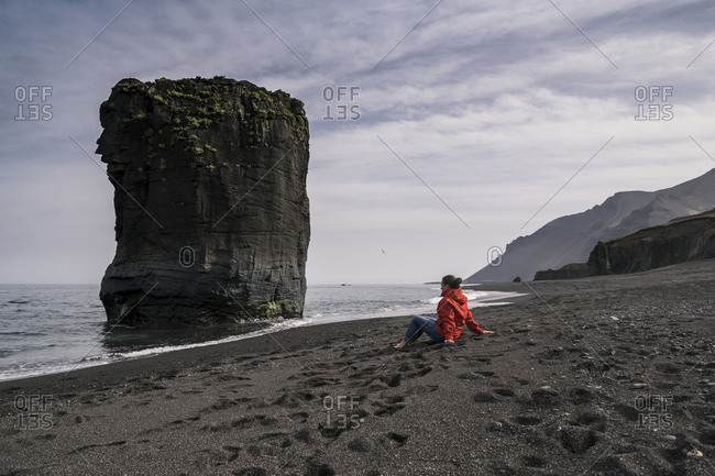 Woman on lava beach in South East Iceland- looking at the sea